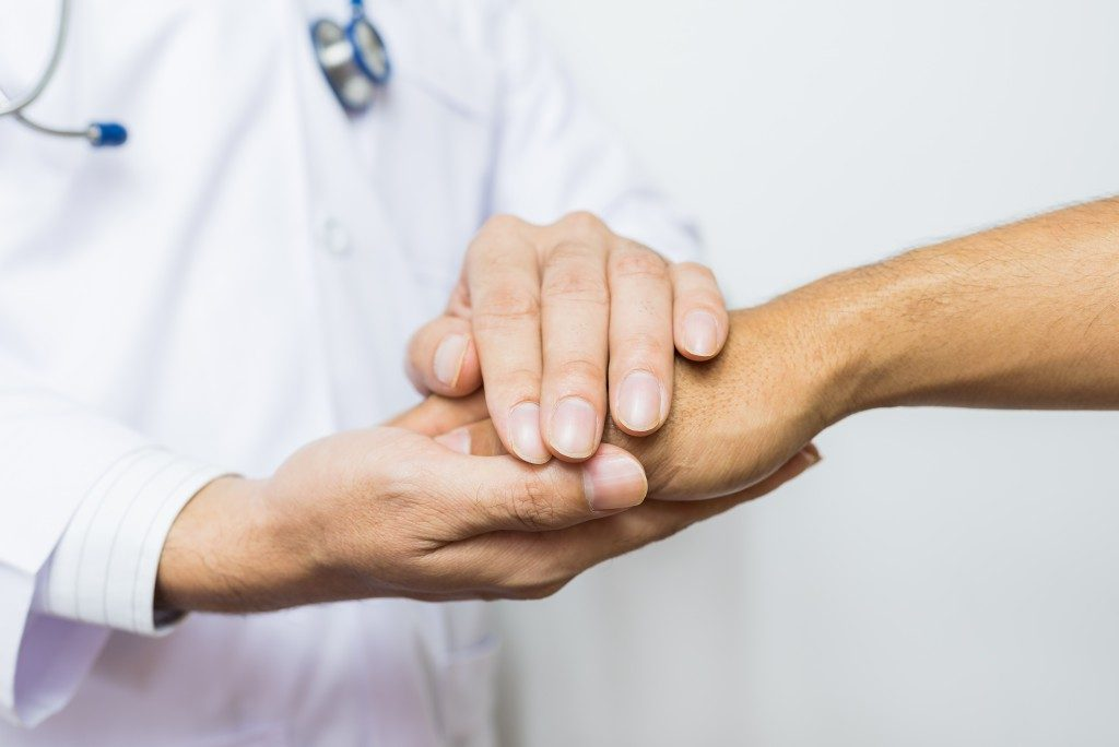 Doctor holding a thankful patient's hand